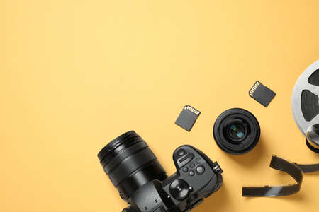Flat lay composition with camera and video production equipment on yellow background. Space for text