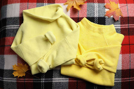 Beautiful yellow warm sweater and leaves on checkered plaid, flat lay