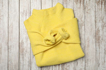 Beautiful yellow warm sweater on white wooden table, top view