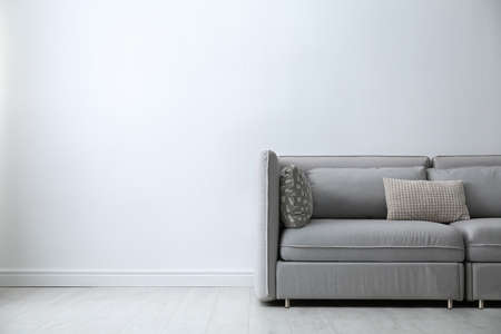 Grey sofa with pillows near white wall in stylish living room interior. Space for text