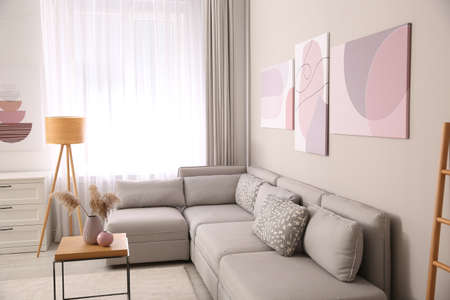 Stylish living room interior with big comfortable sofa and pictures