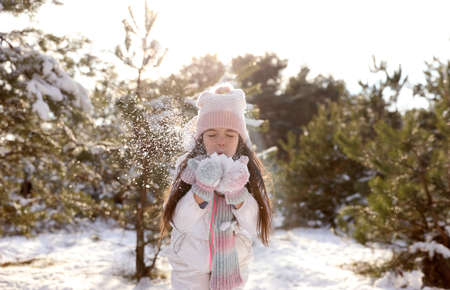 Cute little girl playing with snow in winter forest