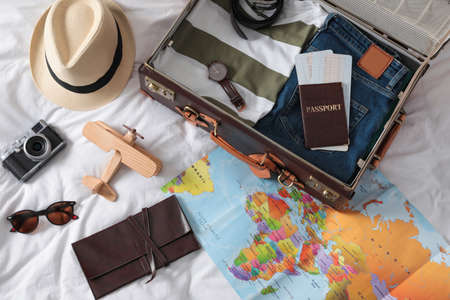 Packed suitcase and travel accessories on white fabric, above view. Summer vacation
