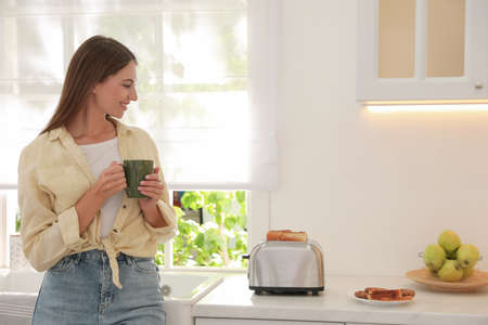 Young woman near toaster with slices of bread in kitchen