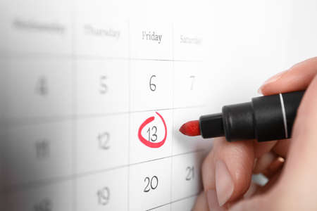 Woman marking Friday 13th on calendar, closeup. Bad luck superstition