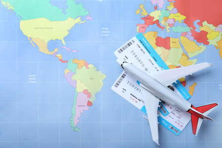 Toy airplane and tickets on world map, flat lay. Travel agency concept