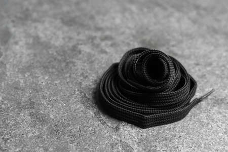 Black shoelace on grey stone background. Space for text Banco de Imagens