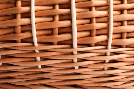 Handmade wicker basket made of natural material as background, closeup view