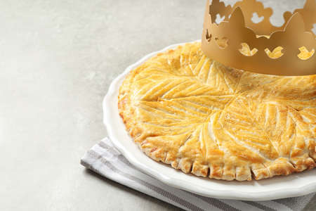 Traditional galette des Rois with paper crown on light grey table, closeup