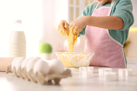 Little girl making dough at table in kitchen, closeup
