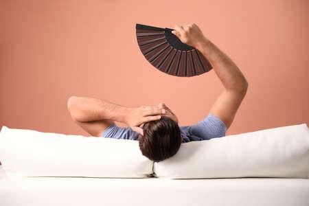 Man with hand fan on sofa. Summer season Stock Photo