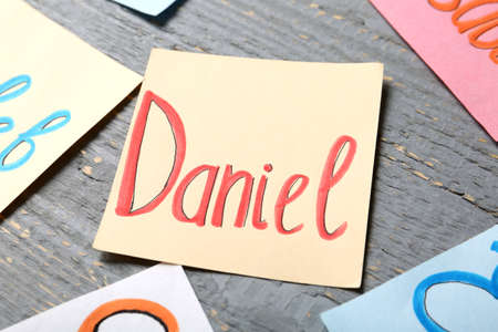 Paper sheet with baby name Daniel on grey wooden table, closeup