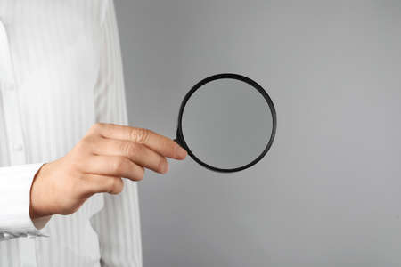 Woman holding magnifying glass on grey background, closeup. Find keywords concept