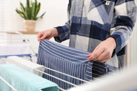 Young woman hanging clean laundry on drying rack at home, closeup