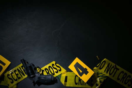 Flat lay composition with gun and crime scene marker on black slate background. Space for text