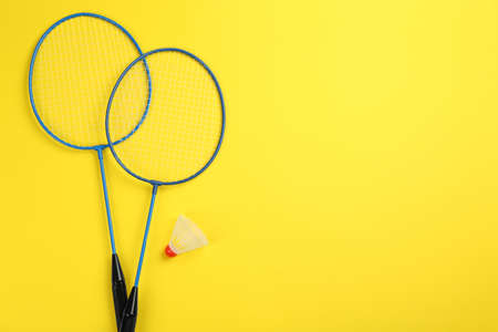 Rackets and shuttlecock on yellow background, flat lay with space for text. Badminton equipment