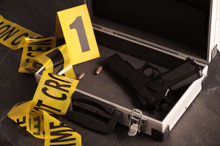 Open case with gun, bullets and crime scene marker on black table, closeup