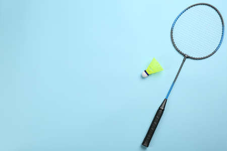 Racket and shuttlecock on light blue background, flat lay with space for text. Badminton equipment