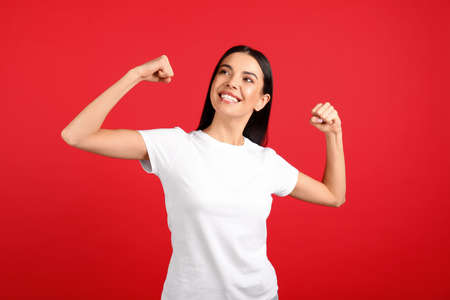 Strong woman as symbol of girl power on red background. 8 March concept Imagens