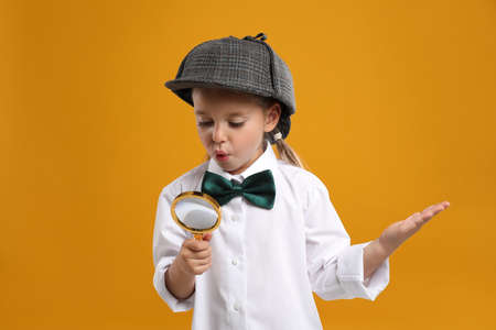 Cute little detective with magnifying glass on yellow background