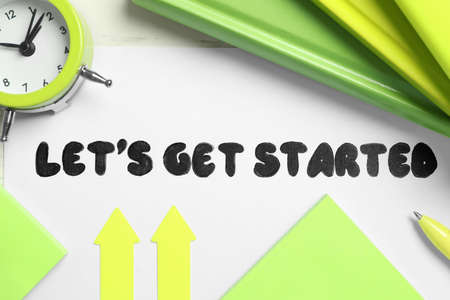 Sheet of paper with phrase Let's Get Started and stationery on white table, flat lay Imagens