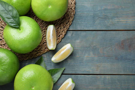 Fresh ripe sweetie fruits on blue wooden table, flat lay. Space for text
