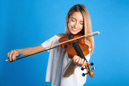 Beautiful woman playing violin on blue background