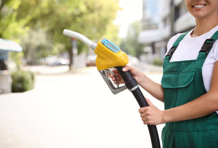 Young worker with fuel pump nozzle at modern gas station, closeup