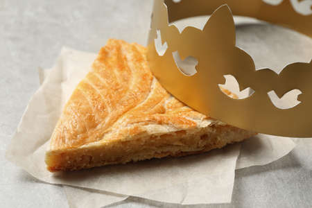Slice of traditional galette des Rois with paper crown on light grey table, closeup Banque d'images