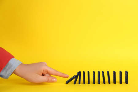 Woman causing chain reaction by pushing domino tile on yellow background, closeup. Space for text