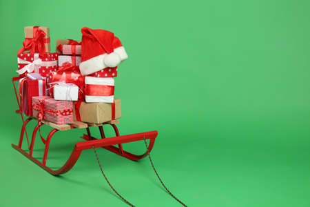 Sleigh with gift boxes and Santa's hat on green background. Space for text