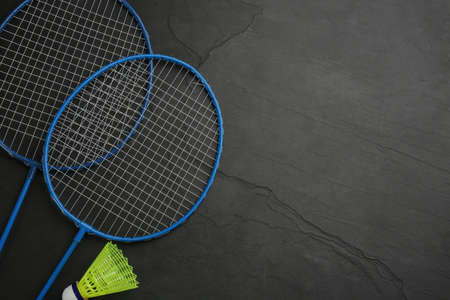 Rackets and shuttlecock on black background, flat lay with space for text. Badminton equipment