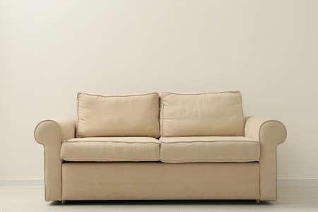 Comfortable sofa near beige wall in living room interior Stockfoto