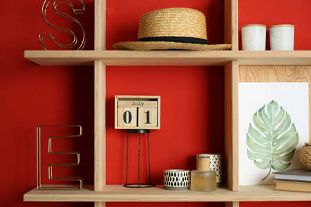 Stylish wooden shelves with decorative elements on red wall