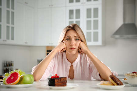 Woman choosing between sweets and healthy food at white table in kitchen Foto de archivo