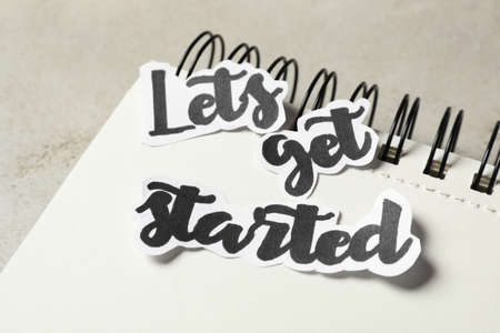 Sheets of paper with phrase Let's Get Started and notebook on grey table, closeup