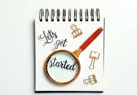 Sheets of paper with phrase Let's Get Started, stationery and magnifying glass on white table, top view