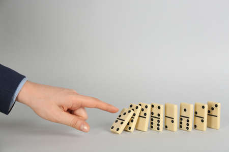 Woman causing chain reaction by pushing domino tile on grey background, closeup. Space for text