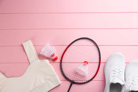 Racket, shuttlecocks and sportswear on pink wooden table, flat lay with space for text. Playing badminton