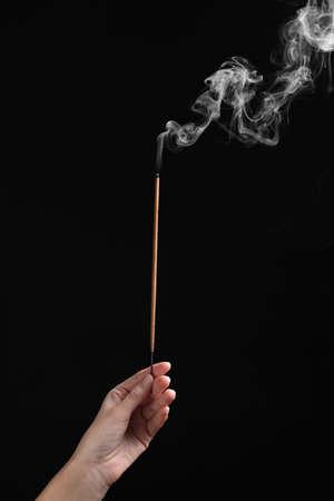 Woman holding smoldering incense stick on black background, closeup