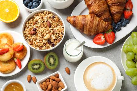 Buffet service. Tasty breakfast served on light grey table, flat lay Stock Photo