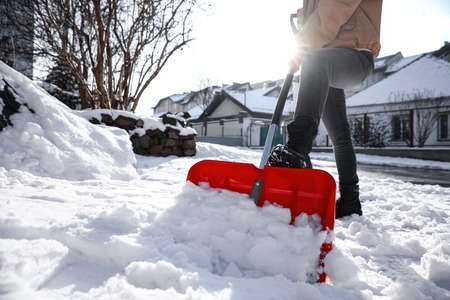 Person shoveling snow outdoors on winter day, closeup