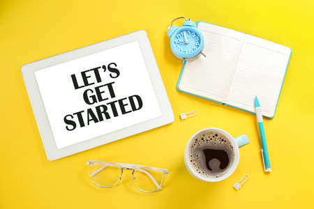 Let's Get Started. Flat lay composition with tablet and stationery on yellow background