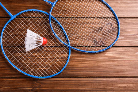 Badminton rackets and shuttlecock on wooden table, flat lay