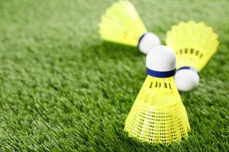 Badminton shuttlecocks on green grass outdoors, closeup. Space for text