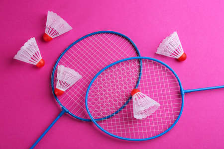 Badminton rackets and shuttlecocks on pink background, flat lay