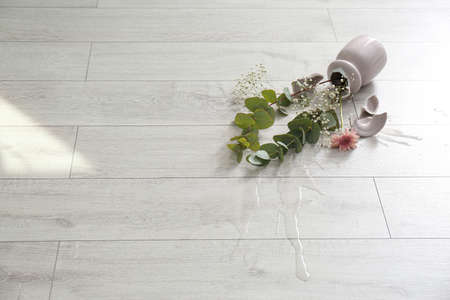 Broken pink ceramic vase and bouquet on wooden floor. Space for text
