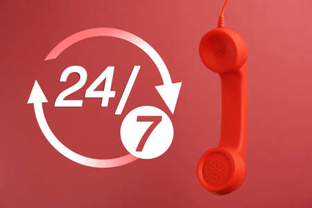 24/7 hotline service. Handset on red background Фото со стока