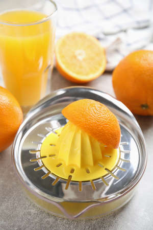 Fresh ripe oranges, juice and squeezer on grey table