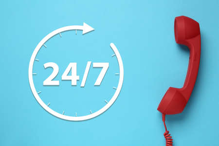 24/7 hotline service. Red handset on light blue background, top view Фото со стока